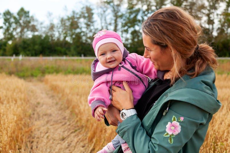 有婴孩的年轻美丽的深色头发的妇女 图库摄影