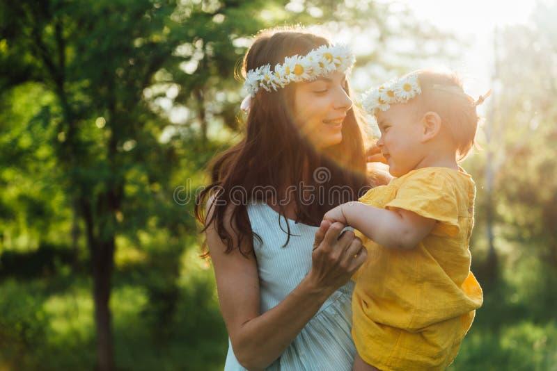 有婴孩的愉快的母亲户外 年轻女人和她的儿童跳舞在日落期间与花 库存照片