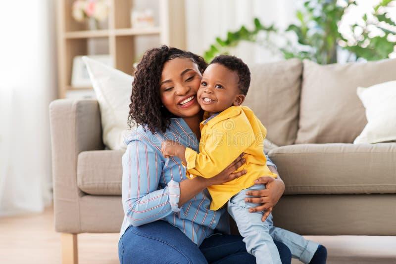 有婴孩的愉快的非裔美国人的母亲在家 库存照片
