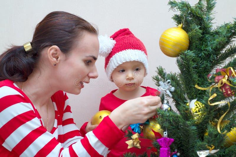 有婴孩的母亲在圣诞树附近 免版税库存照片