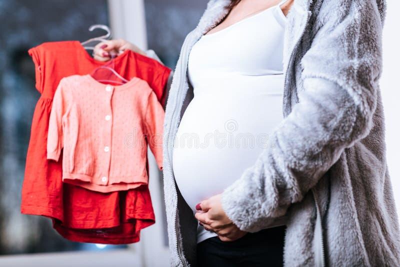有婴孩衣裳的孕妇 免版税库存照片