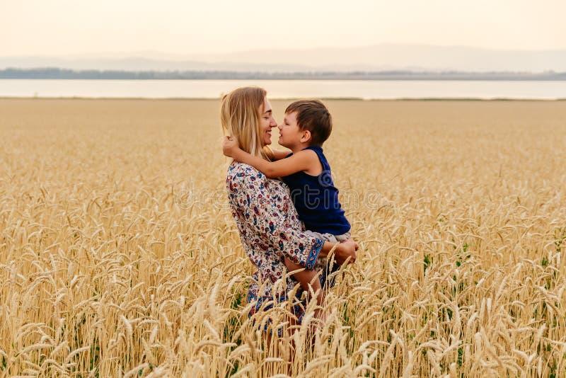 有婴孩面孔的年轻愉快的美丽的母亲在麦田 免版税库存图片