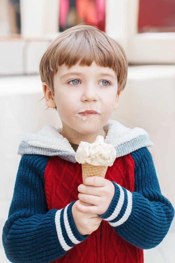 有嫉妒的吃白种人白肤金发的学龄前的男孩在红色毛线衣舔冰淇淋 图库摄影