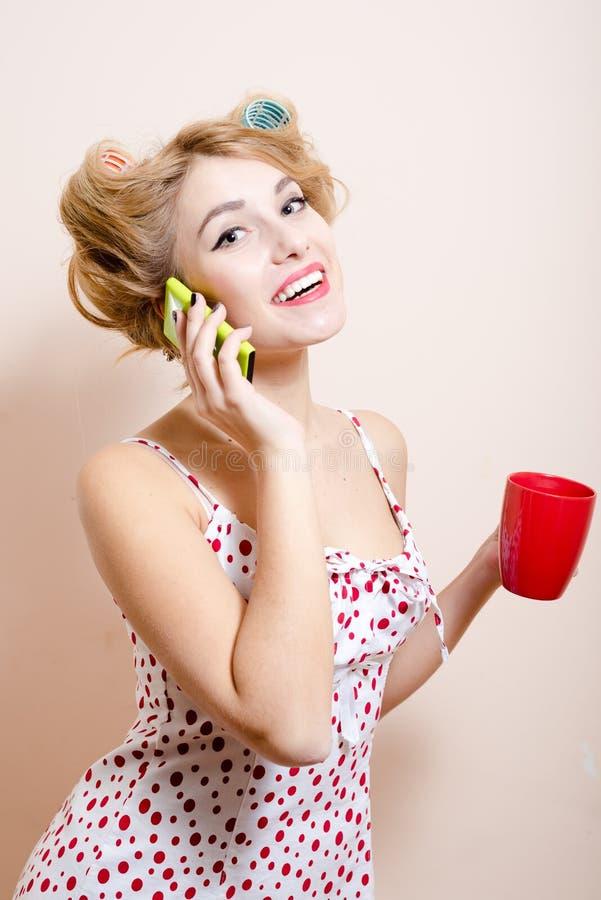 有嫉妒&卷发的人的白肤金发的滑稽的画报妇女发表演讲关于流动愉快的微笑的&看的照相机 库存图片