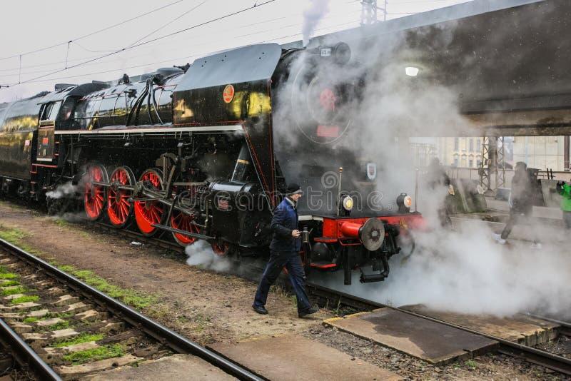 有嫩身分的老黑蒸汽引擎在火车站 免版税库存照片