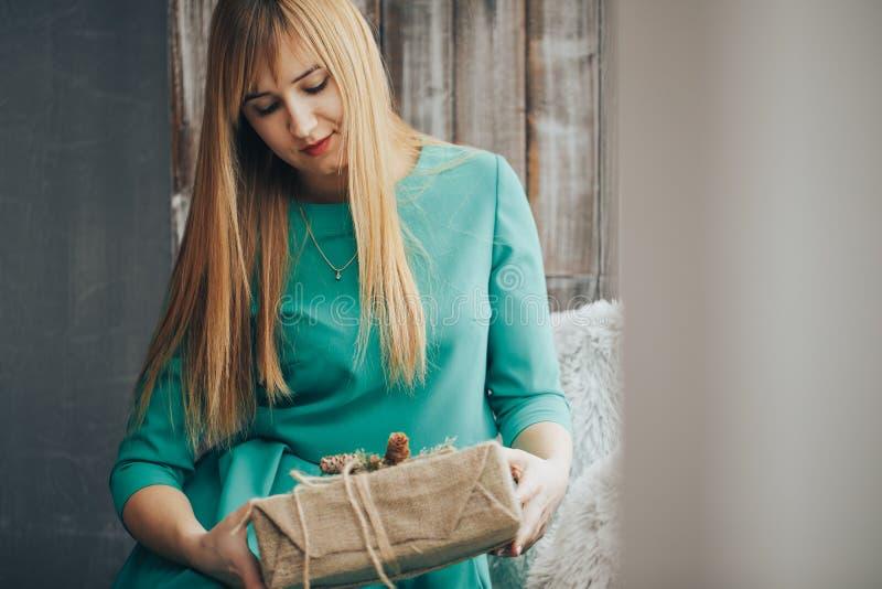 有嬉戏的神色的可爱的快乐的女孩 有礼物的金发美女在她的手上 少妇纵向 图库摄影