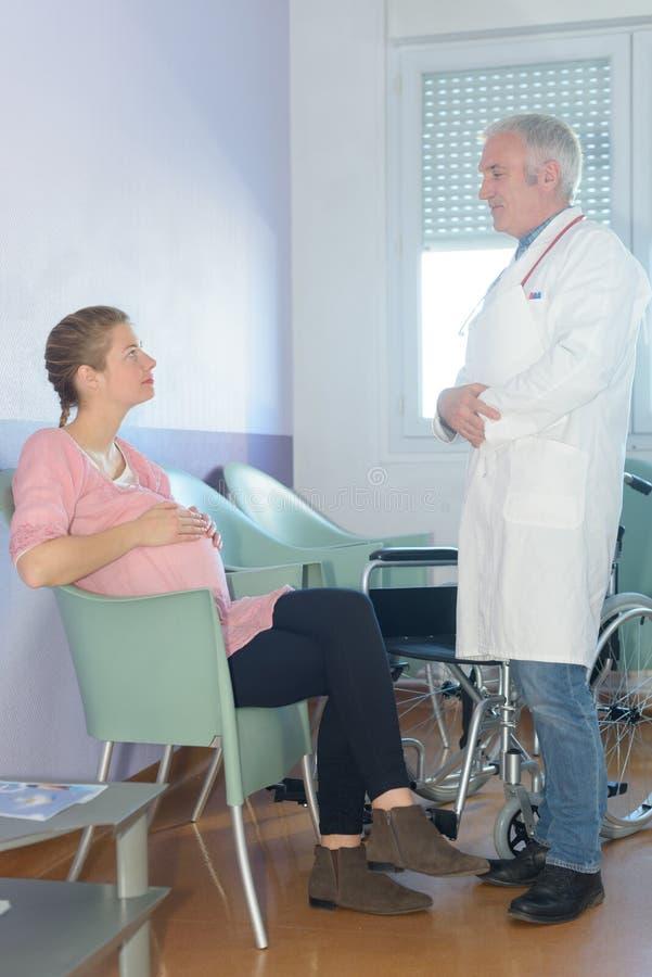 有孕妇的画象确信的男性医生 免版税库存照片