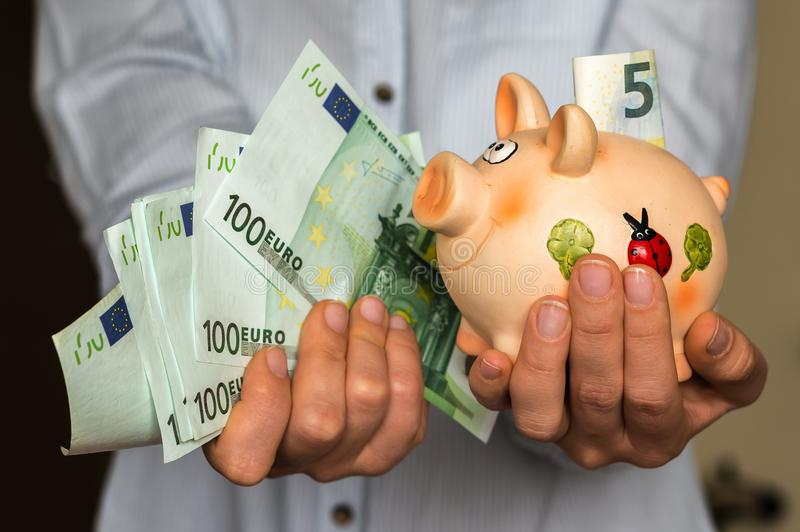 有存钱罐和欧洲钞票的少妇 免版税库存图片