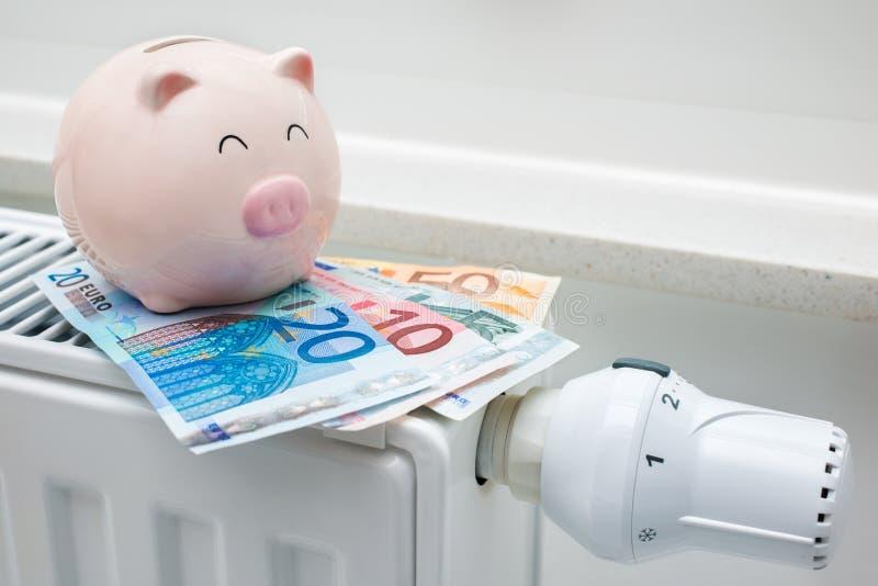 有存钱罐和金钱的热化温箱 库存照片