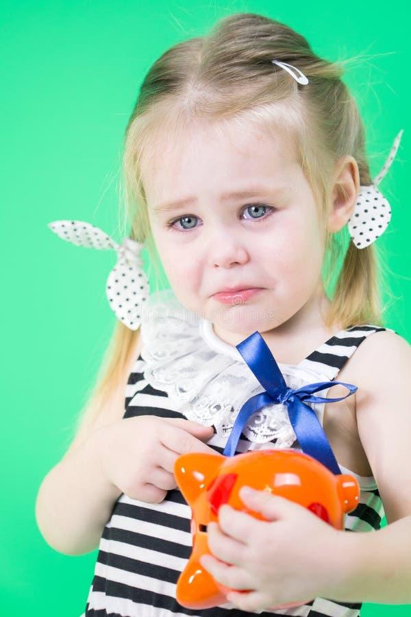 有存钱罐的哭泣的逗人喜爱的小女孩 免版税库存图片