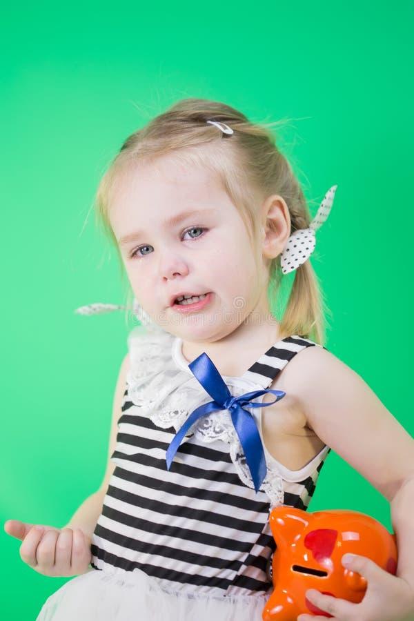 有存钱罐的哭泣的逗人喜爱的小女孩 免版税库存照片