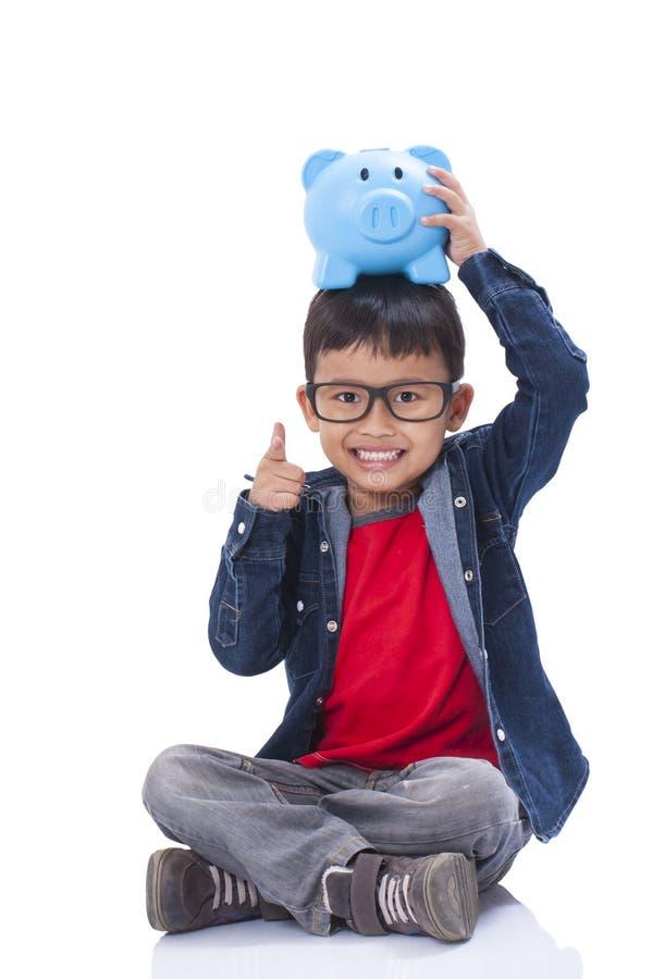 有存钱罐的愉快的男孩 库存照片