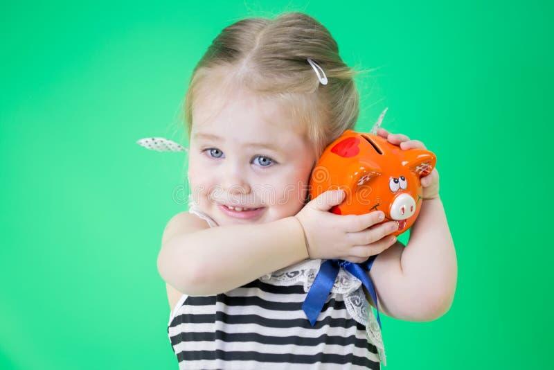 有存钱罐的愉快的逗人喜爱的小女孩 免版税库存照片