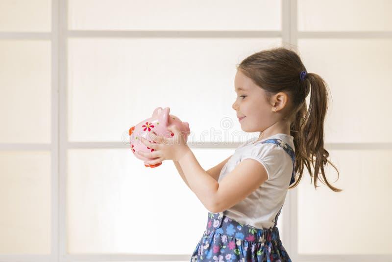 有存钱罐的愉快的年轻小女孩 库存图片