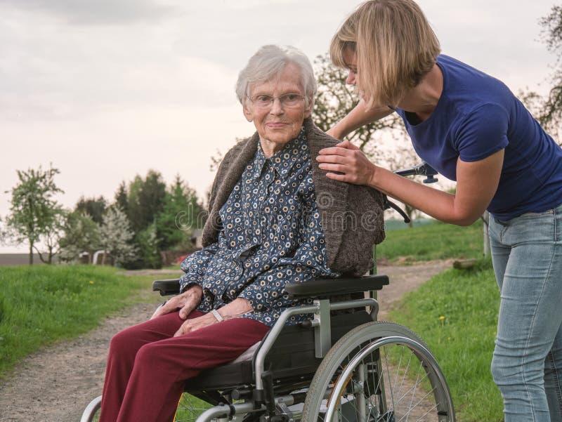 有孙女的残疾资深妇女 免版税图库摄影
