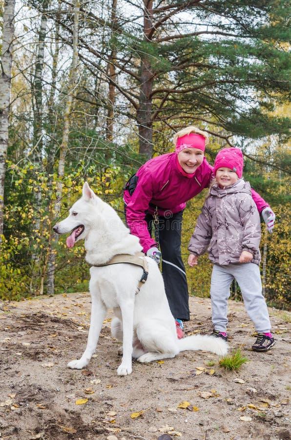 有孙女的老婆婆和狗在秋天公园走 免版税库存照片