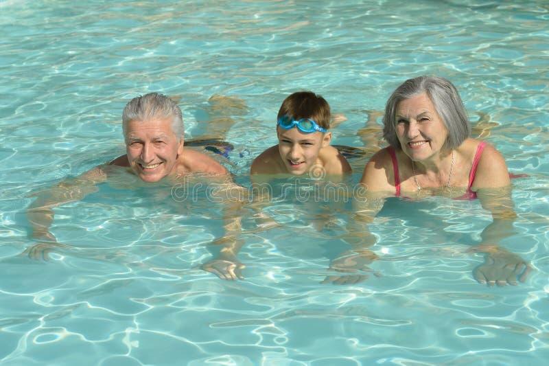 有孙子的祖父母游泳池的 库存照片