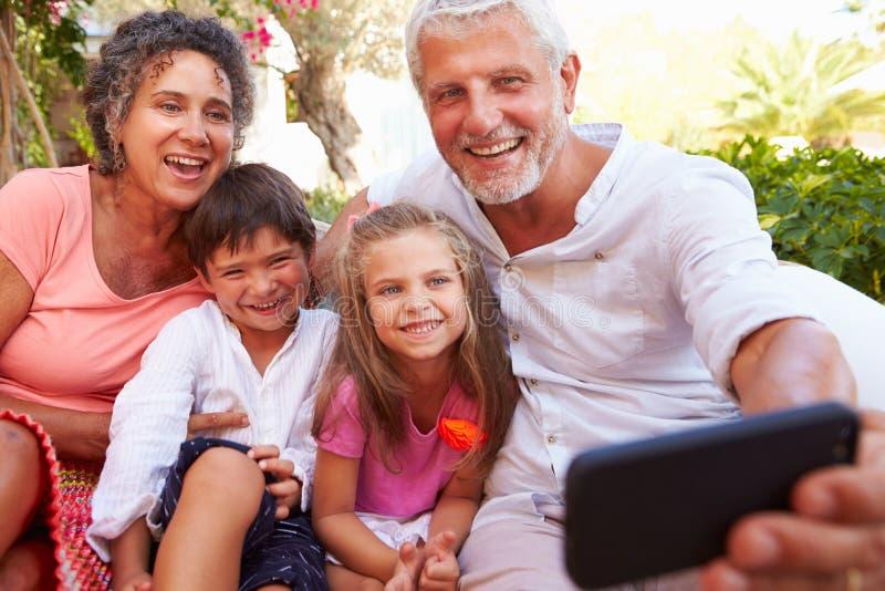 有孙的祖父母在采取Selfie的庭院里 库存照片