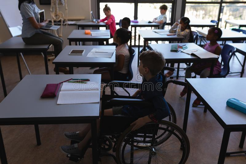 有学习和坐在书桌的同学的功能失效男小学生在教室 库存照片