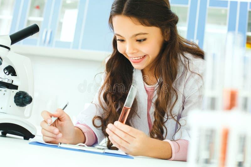 有学会的类小孩在研究项目的学校实验室 免版税库存图片