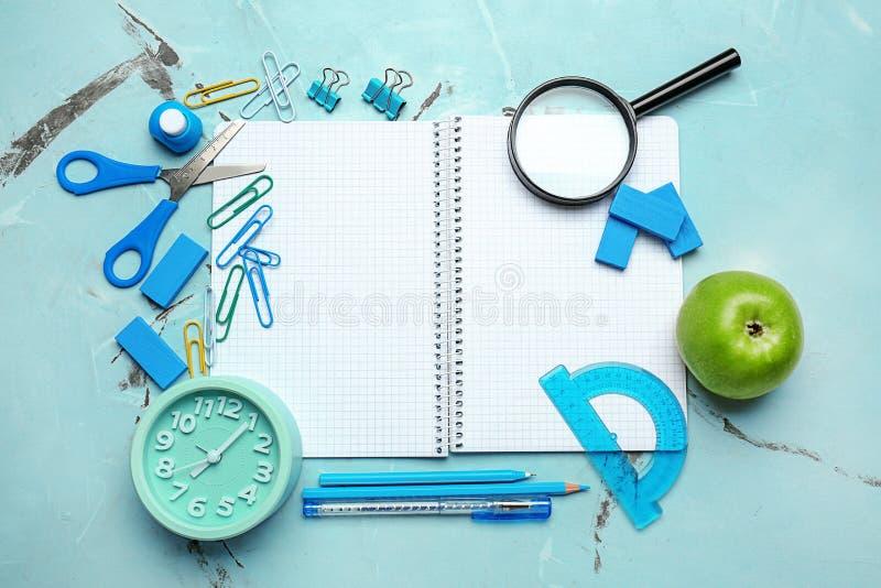 有学校文具和闹钟的开放笔记本在轻的背景 免版税图库摄影