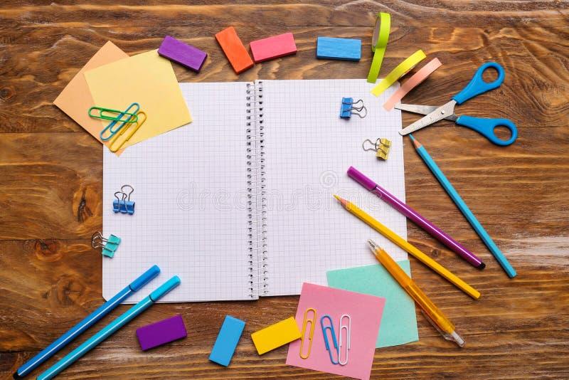 有学校文具的开放笔记本在木背景 免版税库存照片