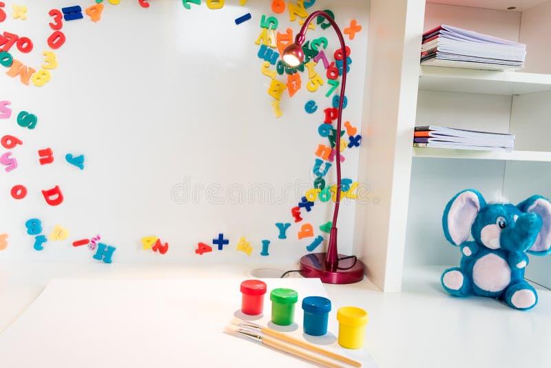 有学校用品、五颜六色的油漆和一个被充塞的蓝色大象玩具的儿童` s学校书桌 库存图片