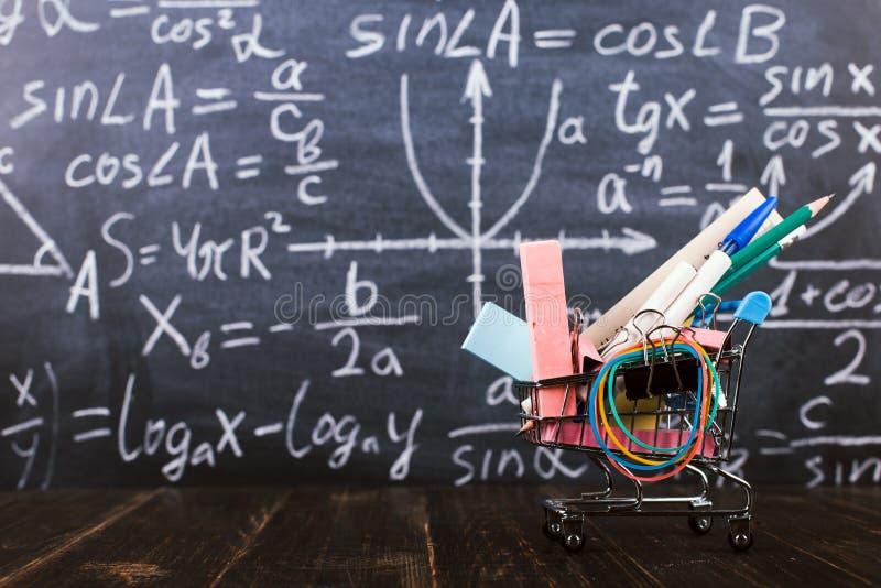 有学校用品的手推车,在以黑板为背景的桌上 回到学校准备的概念 免版税库存图片