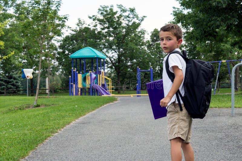 有学校背包和书的孩子走在公园的 免版税库存照片