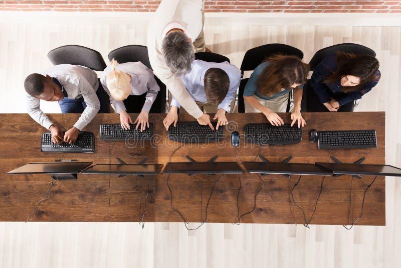 有学生的男老师在计算机室 免版税库存图片