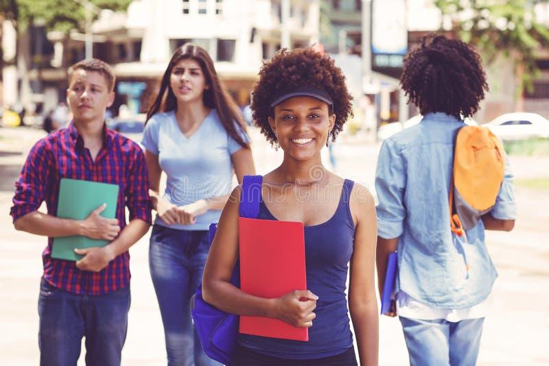 有学生的美丽的非裔美国人的年轻妇女在城市 免版税图库摄影