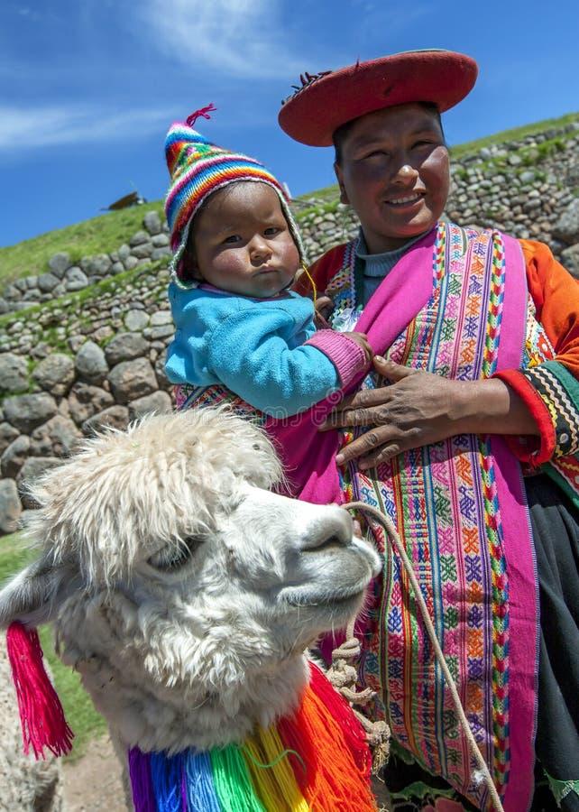 有孩子和骆马的一个秘鲁夫人在库斯科附近在秘鲁 免版税库存照片