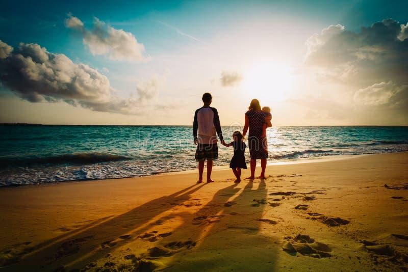 有孩子戏剧的幸福家庭在日落海滩 免版税库存图片