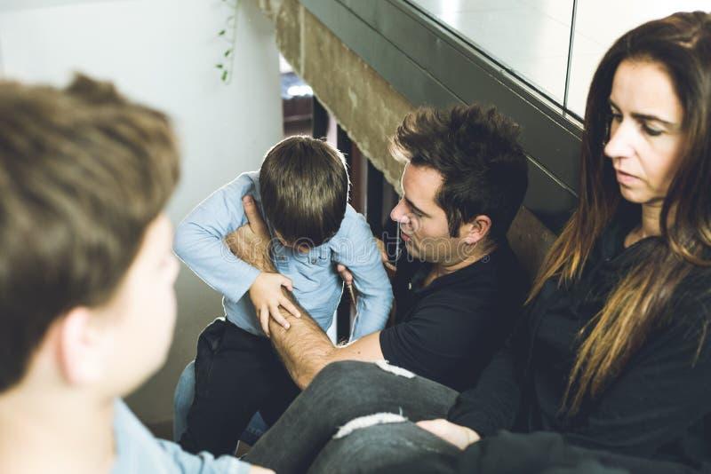 有孩子的一个家庭在家坐愉快的台阶和微笑 可爱的加上孩子在家 免版税库存图片
