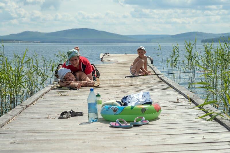 有孩子的一个年轻愉快的家庭在湖附近休息 免版税库存照片