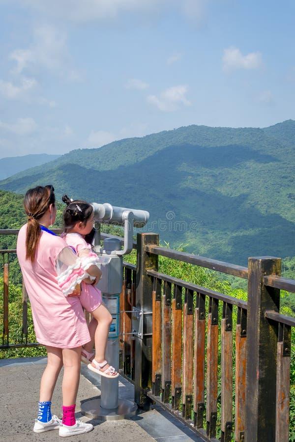 有孩子的一年轻女人通过双筒望远镜观看风景 免版税库存图片
