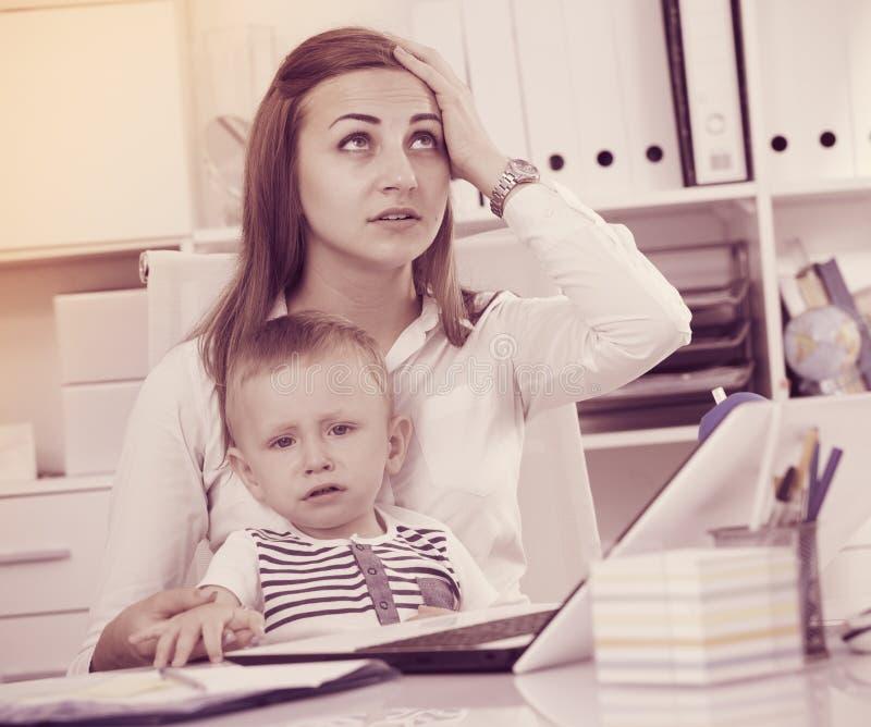 有孩子的为难的女性有问题,当工作时 免版税库存图片