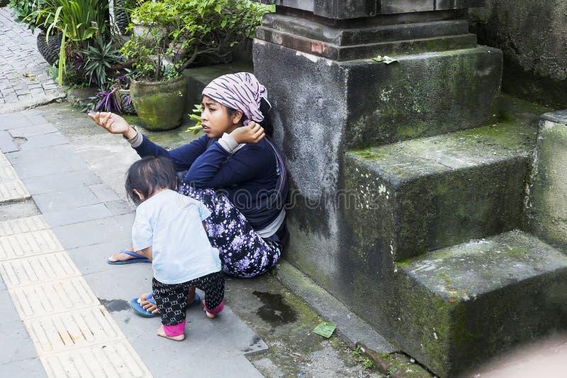 有孩子的叫化子妇女在街道上乞求为施舍 库存照片