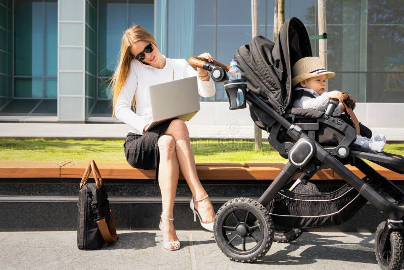 有孩子的女商人谈话在电话和研究膝上型计算机的婴儿推车的 免版税库存照片
