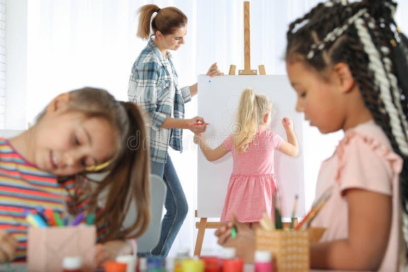有孩子的女老师在绘的教训的画架附近 库存图片