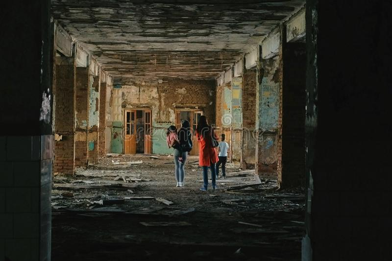 有孩子的妇女在灾害地震以后检查被毁坏的大厦,洪水,火 免版税库存照片