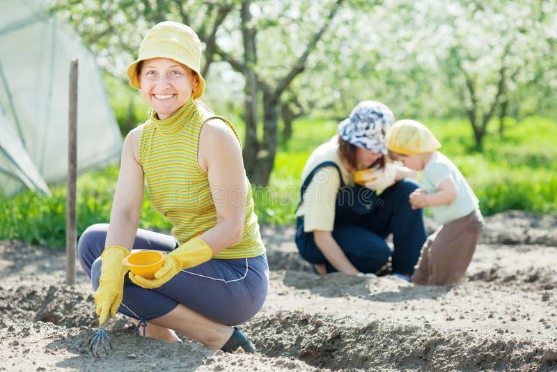 有孩子的妇女在菜园工作 免版税库存照片