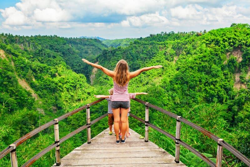 有孩子的妇女在高峭壁的伸出的桥梁站立 免版税图库摄影