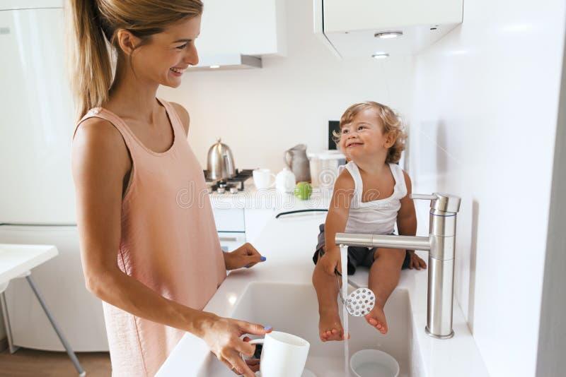 有孩子的妈妈在厨房里 免版税库存照片