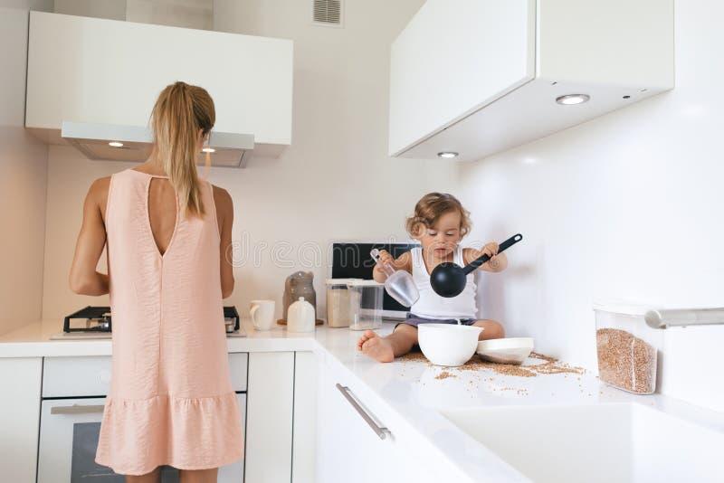 有孩子的妈妈在厨房里 图库摄影