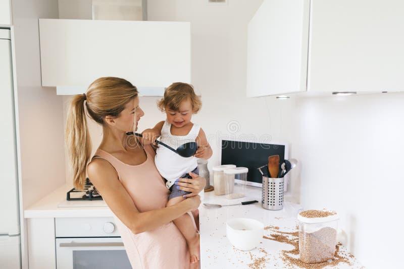 有孩子的妈妈在厨房里 免版税图库摄影