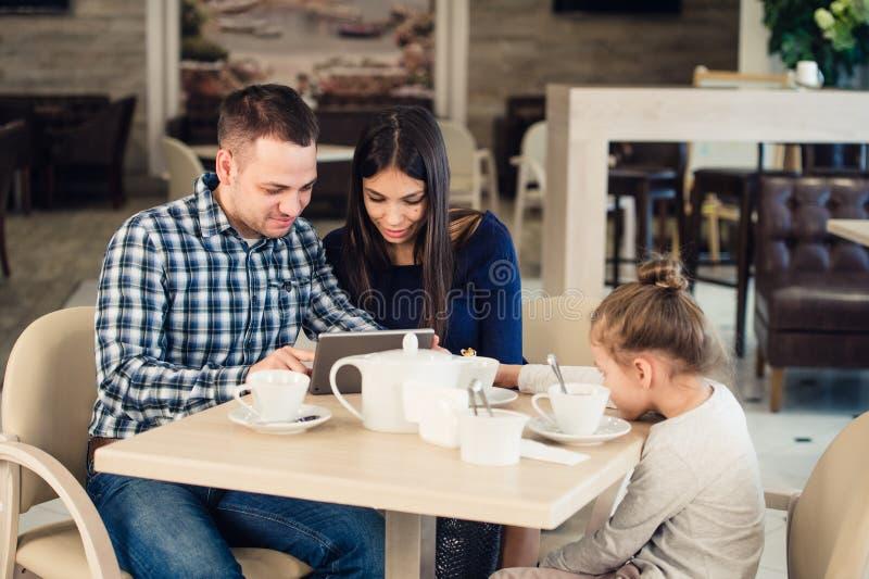 有孩子的家庭咖啡馆的 观看在片剂个人计算机的母亲和父亲,当女孩等待时 免版税库存照片