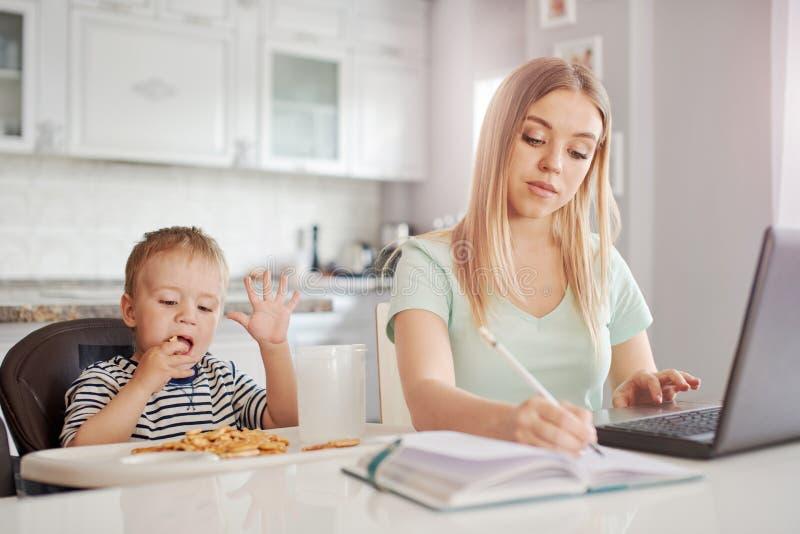 有孩子的工作母亲在厨房里 免版税图库摄影