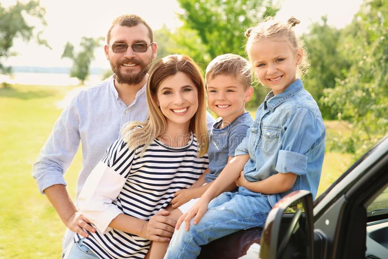 有孩子的愉快的家庭临近汽车户外 免版税图库摄影