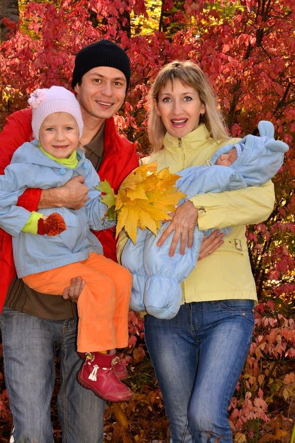 有孩子的愉快的年轻家庭在秋天公园 免版税库存照片